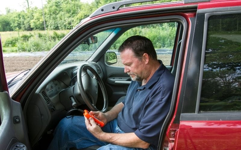 A driver scanning his car with an OBD2 scan tool