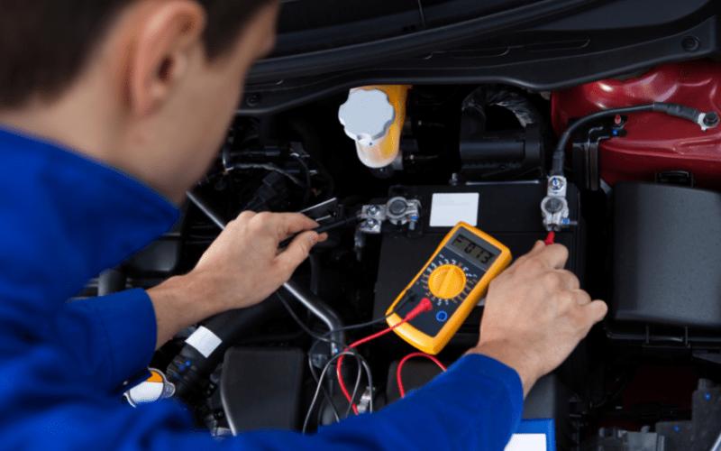 a mechanic testing a battery using a voltmeter