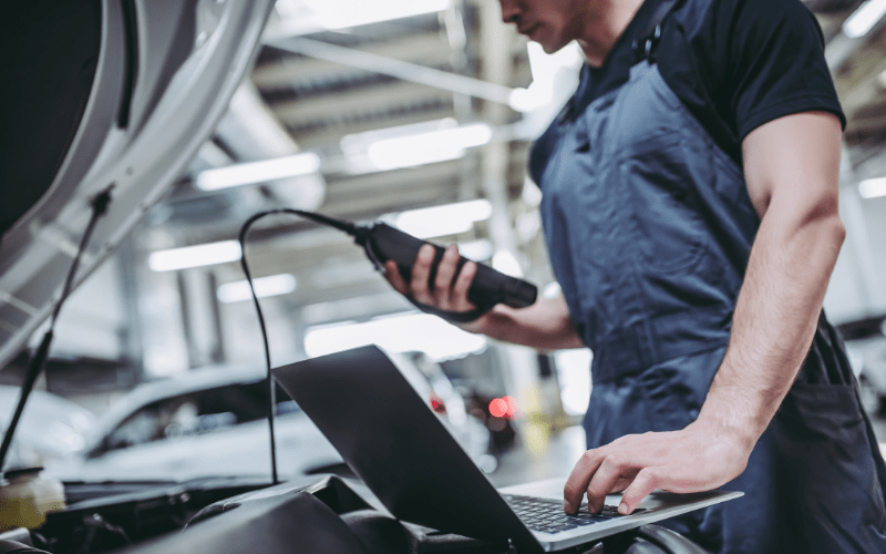 a professional mechanic using a code scanner while working on a car