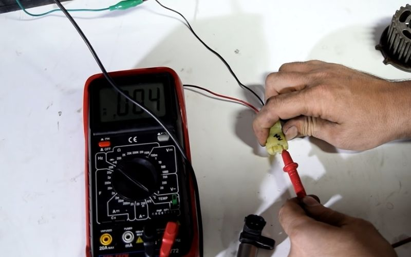 A mechanic taking a reading on the camshaft sensor wiring