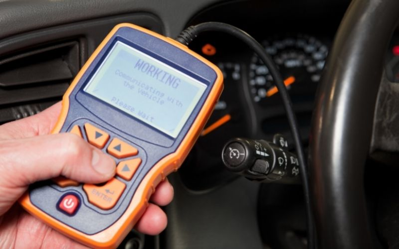 a driver using an OBD2 reader to check his car
