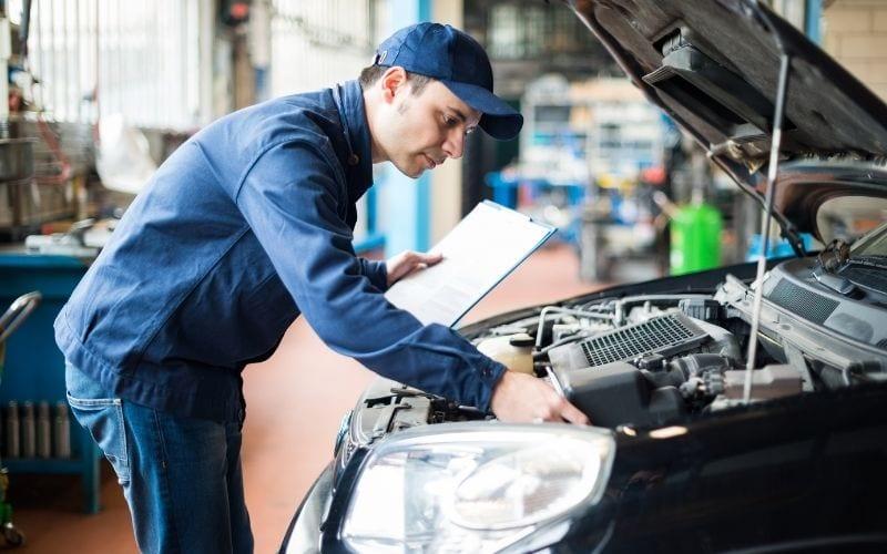 a mechanic going through a checklist of car troubles