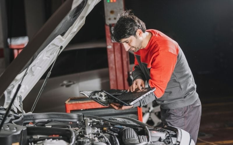 a mechanic referring to his laptop for issues on the car he's working