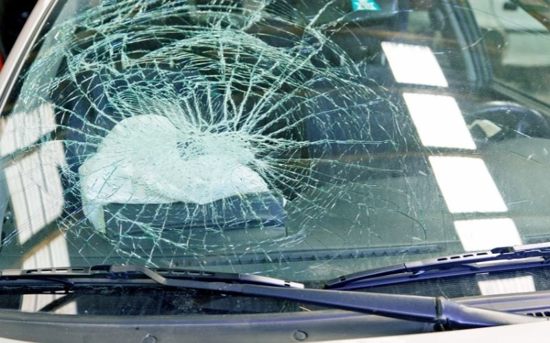 broken windshield and a deployed airbag behind it