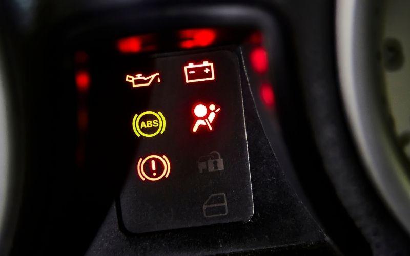 a car dashboard showing various warning lights